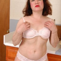 Old redhead mistress doing away with semitransparent clothing and lingerie to pose nude in kitchen