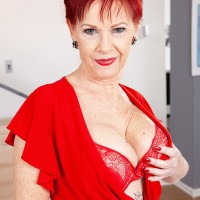 Over Sixty ginger-haired Caroline Hamsel plays with her breasts attired crotchless panties