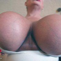 Platinum ash-blonde lady Claudia Marie holds her enormous breasts while sucking on a nip