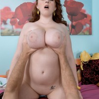 Redhead model Felicia Clover freeing massive knockers and immense butt before sex