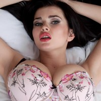 Seductive dark haired MILF Sha Rizel models fully-clothed in a brassieres and panty concoction plus hosiery and high-heels