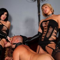 Provocative Dommes Belle Noir and Brianna manhandle collared masculine slave in fetish apparel