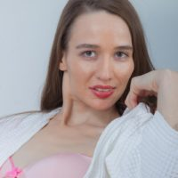 Slender brown-haired girl Rose Nore unveiling flat chest and furry fuckbox from lingerie