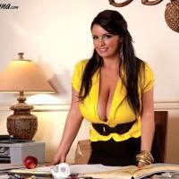 Babe Arianna Sinn releases her gigantic boobies before munching an apple at her desk