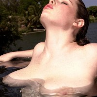 Solo model Desirae plays with her hefty tits while spending time in the water