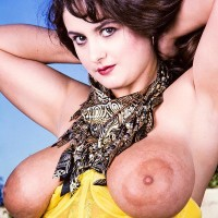 Solo model Justine licks the hard nips of her humungous tits wearing in a garter