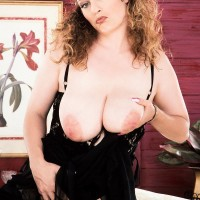 Solo model Traci Burr holds her giant juggs in black lingerie and tights with high-heels
