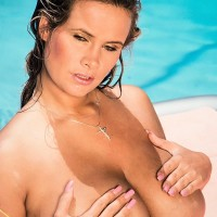 Solo model Trinity Loren displays off her monster-sized tits while taking a dip in the pool