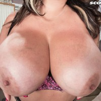 Tatted black-haired MILF Amaya May releases her giant titties from her boulder-holder in a miniskirt