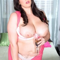 Plumper model Angel DeLuca sets her huge tits free of a pink dress and brassiere in a bedroom