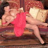 Plumper solo model Arianna Sinn lets her giant breasts loose from a dress in tan nylons