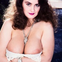 Thick solo model Justine sets her huge tits loose from a sundress while clad milky hosiery