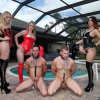 3 Dominatrixes in fetish garb abuse 2 collared male subs on the pool patio