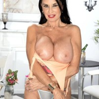 Top mature X-rated actress Rita Daniels exposes her huge boobs and flashes her panties too