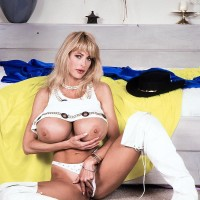 Top X-rated film star Pandora Peaks cups her monster titties with her palms in stripper boots